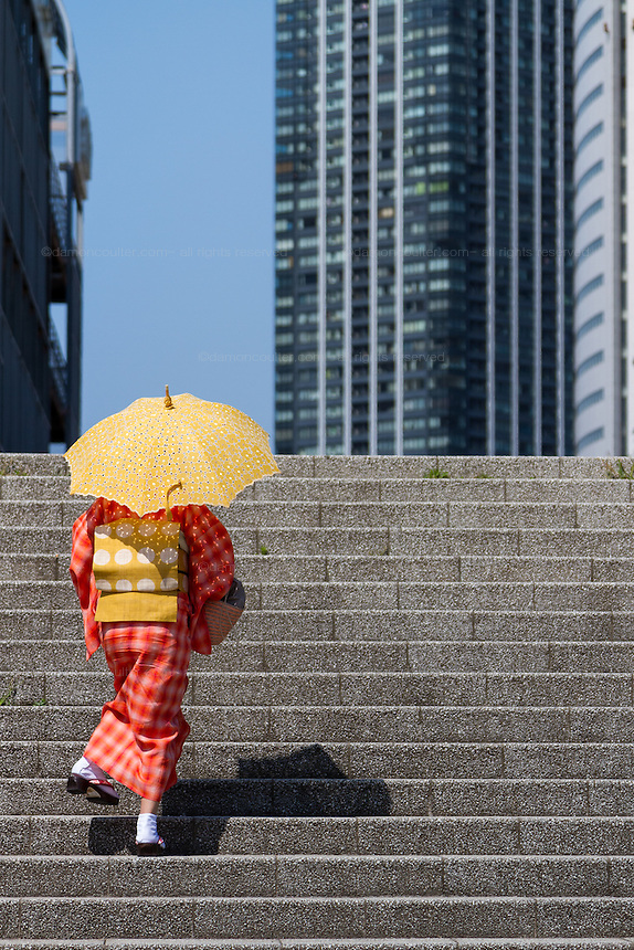 A woman in a red kimono, carrying a parasol, climbs some steps in front of skyscrapers in Odaiba, Tokyo, Japan. Friday June 3rd 2016