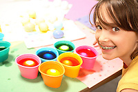 Photo of smiling young girl coloring Easter eggs with several cups of eggs in different, brightly colored dye.