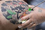 Horiyoshi III (the 3rd) (out of pic), expert Japanese tattooist, tattoos on the body of his German understudy Alex Reinke (also known as Horikitsune), in Horiyoshi's studio in Yokohama, Japan, on Saturday 10th September 2011.