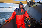 Dutch fisherman on the North Sea holding a Lobster