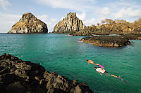 Ecotourism at Bahia dos Porcos in Fernando de Noronha, an archipelago of 21 islands and islets in the Atlantic Ocean, 354 km (220 mi) offshore from the Brazilian coast. Dois Irmaos Island in background. The area is a special municipality (distrito estadual) of the Brazilian state of Pernambuco and is also a UNESCO World Heritage Site.