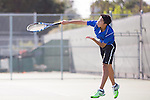 A Los Altos High School tennis player sends a serve back across the court.