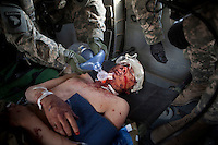 Medics from Charlie Company, Sixth Battalion, 101st Aviation Regiment treat a wounded Afghan National Army (ANA) soldier onboard a US Army medevac helicopter near Kandahar.