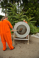 Shawn O'Hanlon shovels nearly finished compost into a screener as E'Ton Littlepage turns the crank to sift the compost. The screener, built by the prison maintainence department out of an old clothing dryer, filters out the trash and wood chips that did not break down and drops the pure filtered compost on the ground below.