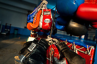 Colorful boxing gloves hung off a rack in the boxing gym in Mexico City, Mexico, 29 April 2011.