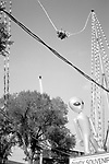 A bungee jump ride springs above power lines while an inflatable alien looks on