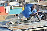 A man in Dabonne, Haiti, builds a temporary shelter for his family, which was left homeless by a January 12 earthquake.