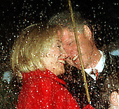 United States President Bill Clinton and first lady Hillary Rodham Clinton seem sharing a happy Christmas memory as rain falls during the National Christmas Tree lighting ceremony on the Ellipse in Washington, DC on December 4, 1997.<br /> Credit: Ron Sachs / CNP