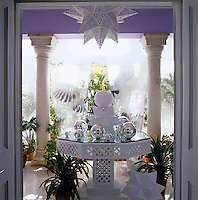 Seen through one of the sets of double doors, the veranda has a latticework table covered in custom-made painted polyhedra and mirrored glass baubles
