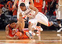 Feb. 2, 2011; Charlottesville, VA, USA; Clemson Tigers forward Milton Jennings (24) fights for the loose ball with Virginia Cavaliers guard Jontel Evans (1) during the game at the John Paul Jones Arena. Virginia won 49-47. Mandatory Credit: Andrew Shurtleff