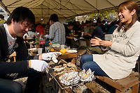 Friends grilling oysters, Bizen city, Okayama Prefecture, Japan, February 2, 2014. The city of Bizen in central Japan is famous for Bizen-ware pottery. It is also one of Japan's main traditional sword making regions, home to Osafune sword-makers and polishers.