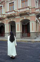 Catholic nun crossing a street in the city of Riobamba, Ecuador