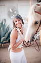 Pretty middle aged woman smiling holding her horse.