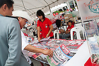 test- Militants are looking at propaganda publications of the Red Shirts movement in Ratchaprasong where hundreds of new militants have signed in those last days. On the right side banknotes given by supporters.