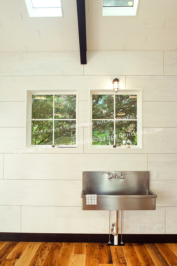 A large stainless steel sink sits against a white wall in a backyard play pavilion.