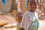A young Fulani woman in Ouagadougou, Burkina Faso, carries a child on her back.