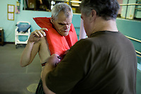 Mike Hebert helps Fernald Developmental Center resident Ronnie Russo (vest) get ready to swim at the Fernald Center Aquatics pool in the Green Building at Fernald in Waltham, Mass., USA. The twins Ronnie and Randy Russo go to the pool twice a week and, with help from Hebert, walk around the pool with light water weights as a way to get exercise and maintain limb strength.  Hebert was an employee at Fernald, but now volunteers as a swim tutor with the twins twice a week.