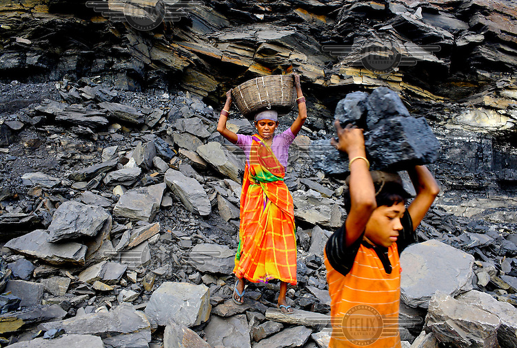 Women and children scavenging coal carry large blocks of the rock that they've taken illegally from an open-cast mine near the village of Bokapahari where a community of coal scavengers live and work. /Felix Features