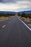 The lines and asphalt of Highway 167 disappear into the vanishing point in eastern California.