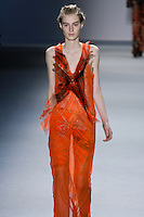 Julia Nobis walks runway in a tangerine silk chiffon crisscross appliqué V-neck gown with vault print flange detail and net lace insets, with tangerine vault print techno stretch bermuda short, from the Vera Wang Fall 2012 Vis-a-gris collection, during Mercedes-Benz Fashion Week Fall 2012 in New York.