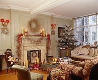 This Victorian drawing room is decorated for Christmas with garlands over the mantelpiece and a small tree by the window