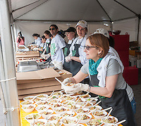 "Volunteers distribute lunch to thousands of visitors to Union Square Park in New York on Tuesday, May 10, 2015 as part of the ""Feeding the 5000"" event organized in part by FeedBack. The public was treated to a free lunch made of high quality produce that normally would have been thrown out from the restaurants and stores that supplied them. ""Feeding the 5000"" was meant to educate the public to help eliminate food waste. (© Richard B. Levine)"