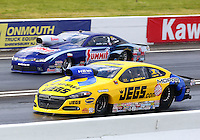 May 31, 2014; Englishtown, NJ, USA; NHRA pro stock driver Jeg Coughlin Jr (near lane) races alongside Jason Line during qualifying for the Summernationals at Raceway Park. Mandatory Credit: Mark J. Rebilas-