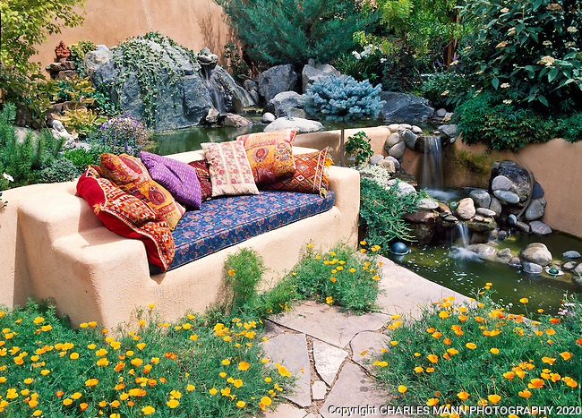 Susan Blevins of Taos, New Mexico, created an elaborate home garden featuring containers, perennial beds, a Japanese themed path and a regional style that reflects the Spanish and pueblo architecture of the area. Colorful pillows add pizaz to bench in a sunken niche by a waterfall. hnche