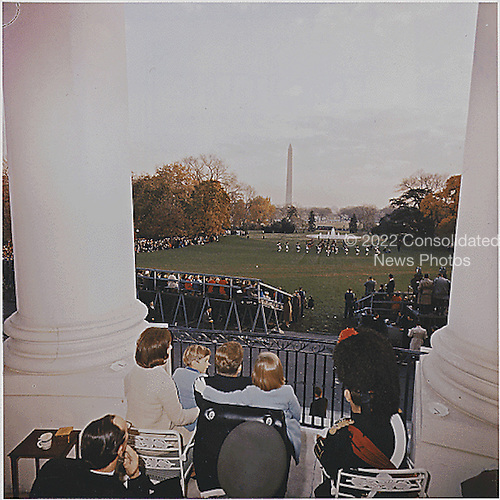United States President John F. Kennedy and Family watch the Black Watch Tattoo perform on the South Lawn from the Truman Balcony of the White House in Washington, DC on November 13, 1963.  First Lady Jacqueline Kennedy,  John F. Kennedy ,Jr., Caroline Kennedy, Major Wingate Gray, Ambassador of Great Britain David Ormsbey-Gore, spectators.<br /> Credit: White House via CNP