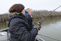 NWA Democrat-Gazette/FLIP PUTTHOFF <br /> Denise Rivers hangs on tight      Jan. 16, 2016 while battling a big striper. Kevin Rivers stands by to net the fish.