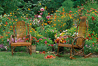 two handbuilt bent rockers in front of blooming pastel garden with baskets of fresh fruit and vegetables