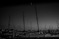 The harbor at San Leandro Marina in black and white with a crescent moon holding watch.