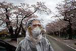 """A woman, who went by the name of Miki, walks along a street famed for having one of Japan's longest cherry blossom """"tunnels"""" in Tomioka, Fukushima Prefecture, Japan on Wednesday 20 April  2011. The woman, a former nuclear power plant employee, was visiting the town -- which falls inside the now legally enforced evacuation zone -- to see the famed cherry trees and pick up some belongings from her home..Photographer: Robert Gilhooly"""