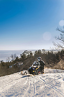 Snowmobiles high above Lake Superior atop the Mount Marquette overlook in Marquette, Michigan.<br /> G