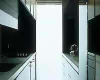 This small black contemporary kitchen has stainless steel work surfaces