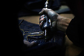"""A worker drills a pair of jeans in Mr Huang's factory in Zhongshan city, China..This picture is part of a photo and text story on blue jeans production in China by Justin Jin. .China, the """"factory of the world"""", is now also the major producer for blue jeans. To meet production demand, thousands of workers sweat through the night scrubbing, spraying and tearing trousers to create their rugged look. .At dawn, workers bundle the garment off to another factory for packaging and shipping around the world..The workers are among the 200 million migrant labourers criss-crossing China.looking for a better life, at the same time building their country into a.mighty industrial power."""