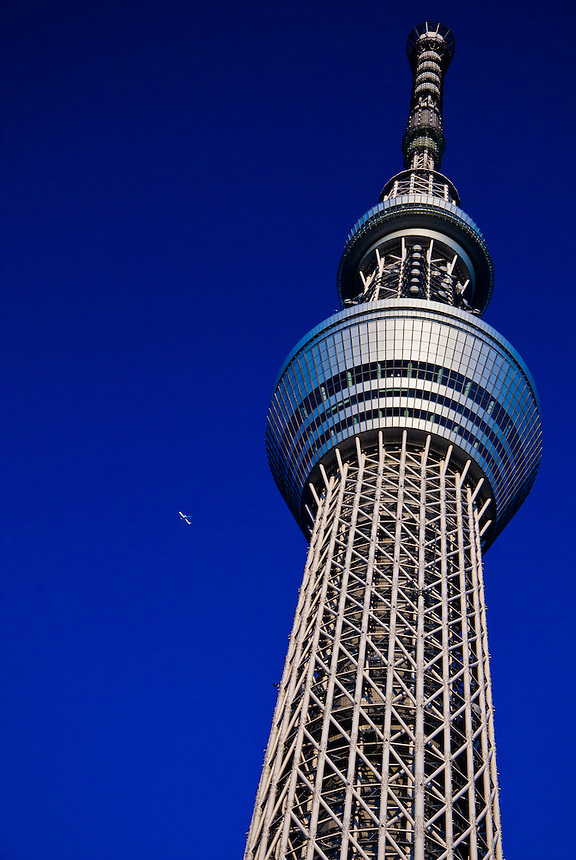 "Tokyo Sky Tree against a brilliant blue sky with airplane. At 634m its the Worlds highest ""free standing"" broadcasting tower."