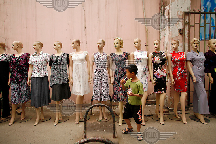 A boy eats a popsicle near a line of mannequins displaying clothes for sale in Chengdu.