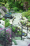 a difficult trouble sunken space between house and retaining wall has been turned into a private quiet sitting area complete with flagstone path, lush perennial beds, and a water feature