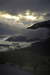 Clouds, mountain silhouetted trees early morning sunrise. Imst district, Tyrol/Tirol, Austria. Alps.