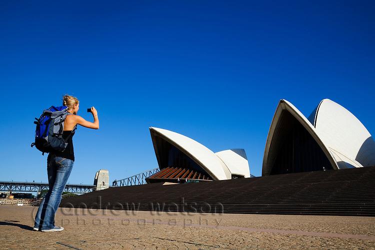A backpacker photographs the Sydney Opera House.  Sydney, New South Wales, AUSTRALIA.