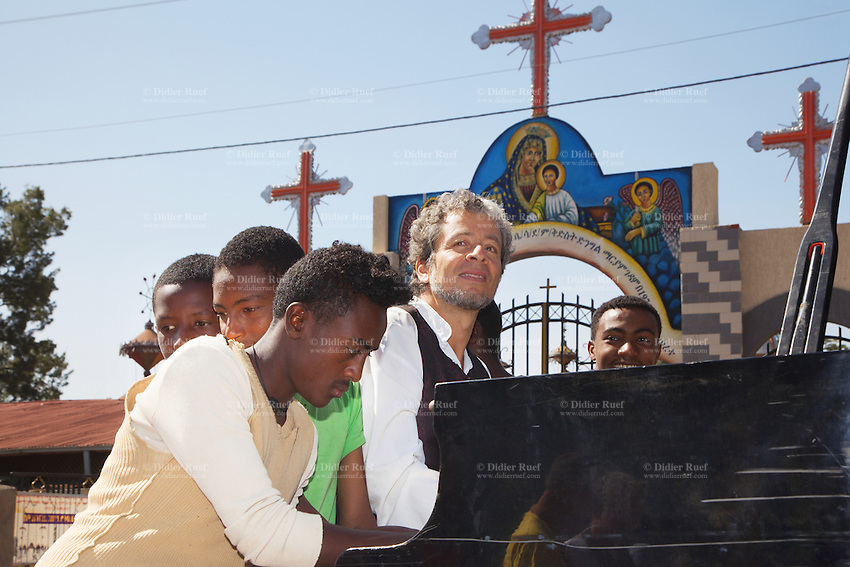 """Ethiopia. Oromiya Region. Walliso. The Christian Cross at a church's entrance. Colorful paintings with the Virgin Mary. Marc Vella is a french musician and a nomadic pianist. Over the last 25 years he has travelled with his Grand Piano in around forty countries to celebrate humanity. Creator of """"La Caravane amoureuse"""" (The Caravan of Love) he takes people with him to say """"I love you"""" to others and """"lovingly conquered"""" their hearts and souls. Marc Vella and a group of ethiopian young men play an improvised duet-playing - one piano and four hands. Mary, also known as St Mary the Virgin, the Blessed Virgin Mary, Saint Mary, Mary the Mother of God, or the Virgin Mary was the mother of Jesus. The Christian Cross, seen as a representation of the instrument of the crucifixion of Jesus, is the best-known symbol of Christianity. 16.11.15 © 2015 Didier Ruef"""