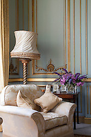 Detail of an armchair in the drawing room upholstered in a rich cream and gold patterned fabric, behind which is a carved standard lamp complete with ruched lampshade