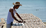 A man turns fish as they dry in the sun in Estancia, a village in the Philippines that was hit hard by Typhoon Haiyan in November 2013. The storm was known locally as Yolanda. The National Council of Churches of the Philippines, a member of the ACT Alliance, has assisted members of the community as they have recovered from the emergency.