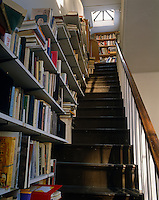 Additional book storage has been created by constructing shelves that use the staircase to support the weight