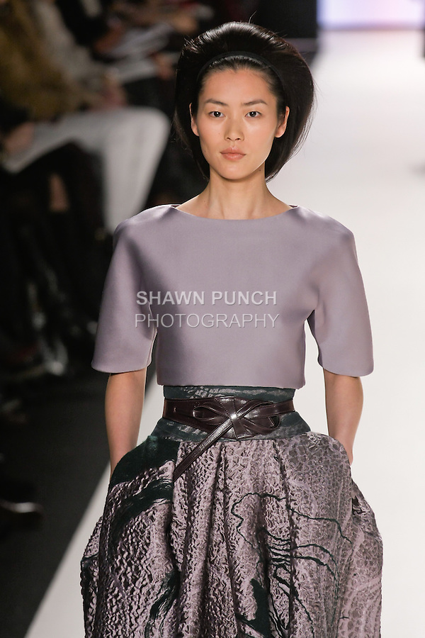 Liu Wen walks runway in a London lilac duchess satin cropped top with a London lilac swirl jacquard ball skirt, imperial purple leather wrap belt, from the Carolina Herrera Fall 2012 collection, during Mercedes-Benz Fashion Week Fall 2012 in New York.