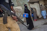 Pakistani polio vaccination team administering polio drops to children under tight security, during door-to-door 'Anti-polio campaign' in Karachi, Pakistan on Jan. 19, 2015