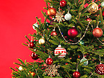 Closeup of Christmas tree colorful decoration on bright red background