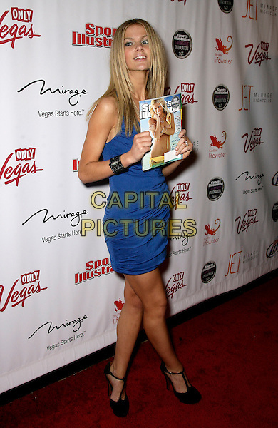BROOKLYN DECKER.Sports Illustarted Swimsuit On Location Party Hosted by Jet Nightclub at the Mirage Resort Hotel and Casino, .Las Vegas, Nevada, USA, .10th February 2010..SI full length blue dress holding magazine black t-bar shoes .CAP/ADM/MJT.© MJT/AdMedia/Capital Pictures.