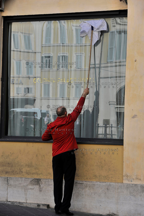 Roma 26 Aprile 2010.Piazza Montecitorio.Un addetto alle pulizie di un albergo pulisce la vetrata esterna..Rome April 26, 2010.Piazza Montecitorio.An insider of a hotel maid, cleaning the window outside.